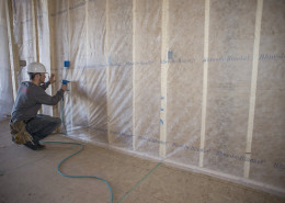 Installer stapling fine mesh to face of the wall studs